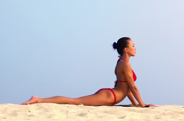 Image of female in red bikini sunbathing on sandy beach during vacation