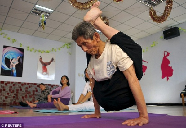 Hou Zhenshan shows an arm balance to his class